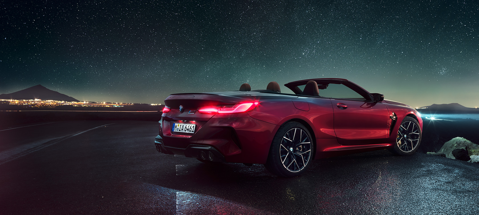 BMW M8 Competition Convertible in Motegi Red metallic with open softtop, three-quarter rear view, standing under starry sky.